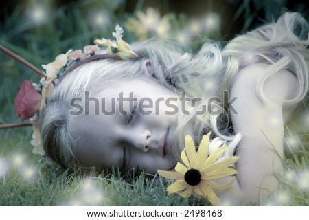 A woodland fairy sleeps peacefully as fireflies act as her nightlights. - stock photo
