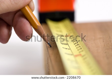A woodworker measures the mark for his cut - stock photo