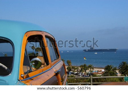 A woody retro classic car with the USS Ronald Reagan in the background in Santa Barbara, California. - stock photo
