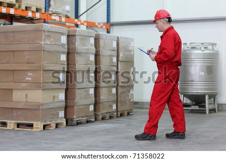 A worker checking stocks in a company warehouse. - stock photo