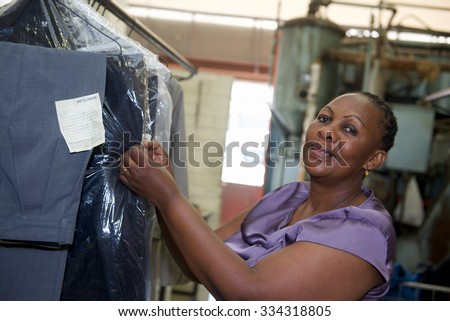 A worker checks cleaning clothes in laundry - stock photo