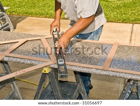 A worker checks the size of a granite slab for use in a suburban home kitchen remodel - stock photo