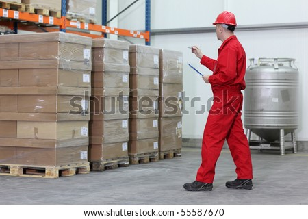 A worker counting stocks in a company warehouse. - stock photo