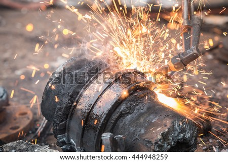 A worker cutting steel using metal torch - stock photo