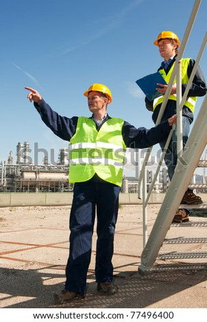 A worker discussing procedures with another worker in front of a petrochemical refinery - stock photo