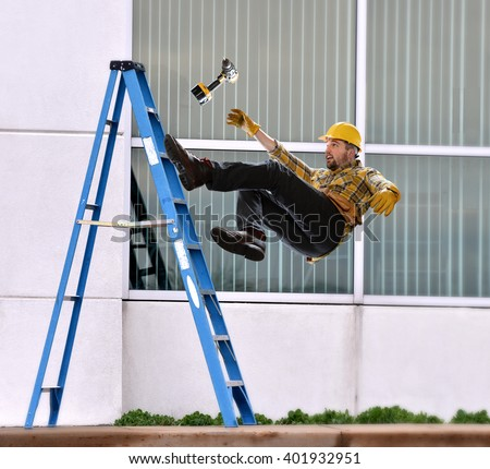A worker falls from ladder while making repairs to building - stock photo