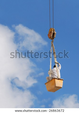 A worker hanging on a steel cable - stock photo