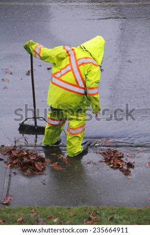 A worker in a safety suit cleans debris from the opening of a sewer after heavy rains/Street Sweeper Cleaning Flooded Sewer Drain/A street sweeper clears a clogged sewer drain - stock photo