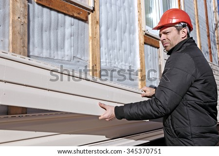 A worker installs panels beige siding on the facade of the house - stock photo