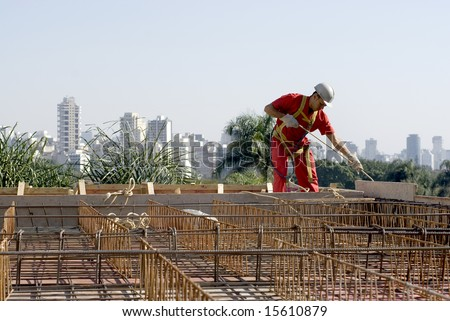 A worker is standing at the top of a building being constructed.  He is hauling materials up to him on a rope.  The site he is working is level with the cities skyline.  Horizontally framed shot. - stock photo