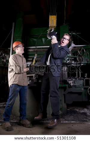 A worker laughing while hanging his boss by his arm on a crane. - stock photo