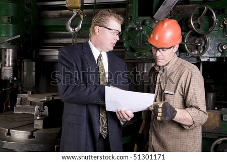 A worker looking and listening to his boss explain what is on the blue prints. - stock photo