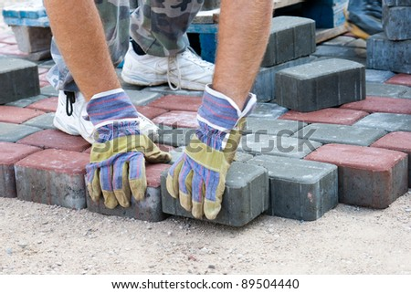 a worker made a sidewalk from bricks - stock photo