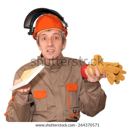 A worker man in overalls, helmet with the raised visor offers a choice: a book or a pair of gloves. The choice between work and learning, mental or physical labor.  - stock photo