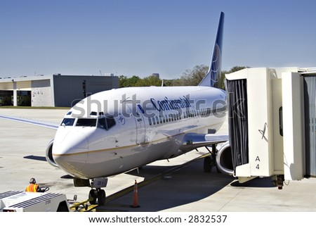 A worker moves large commercial jet into position at Tampa Florida airport.