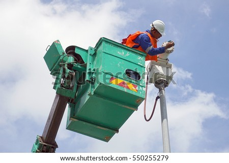 A worker on a sky lift doing maintenance work on an explosive proof security camera.