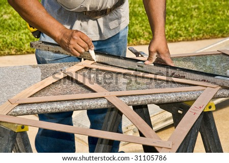A worker prepares a slab of granite to be used for a kitchen remodeling - stock photo