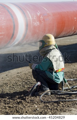 A worker sandblasting the weld in preparation for coating during pipeline construction - stock photo