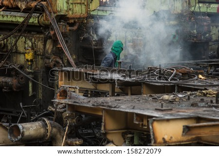A worker uses a oxygen acetylene cutting torch to cut a large metal object in old to recycle - stock photo