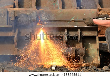 A worker uses a oxygen acetylene cutting torch to cut a large metal object into manageable pieces at a metal recycling plant
