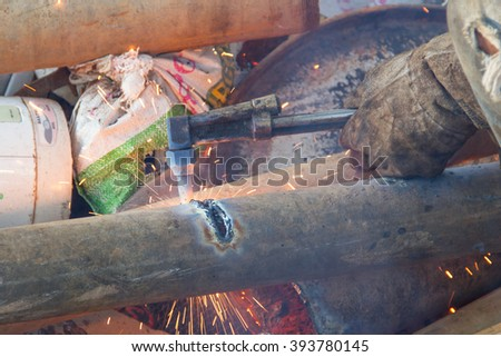 A worker uses a oxygen acetylene cutting torch to cut scrap at twilight
