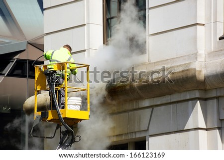 a worker washes the facade of the building - stock photo