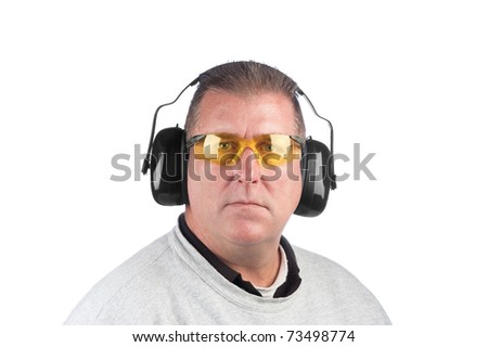 A worker wearing yellow safety glasses and hearing protection. - stock photo