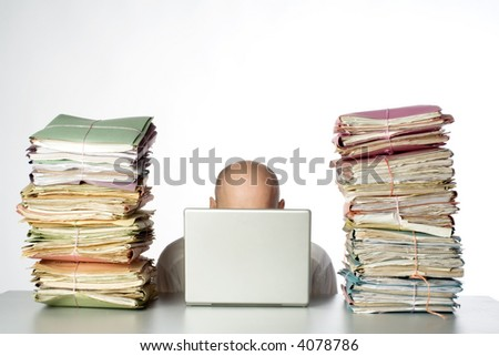 A worker with a pile of folders on his desk. - stock photo