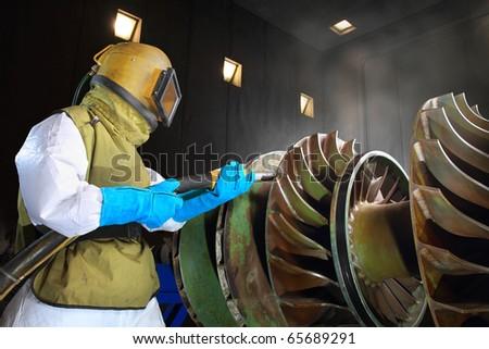 A worker working in a sandblast workshop - stock photo