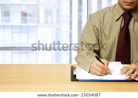 A working businessman writing on a notepad at the office - stock photo
