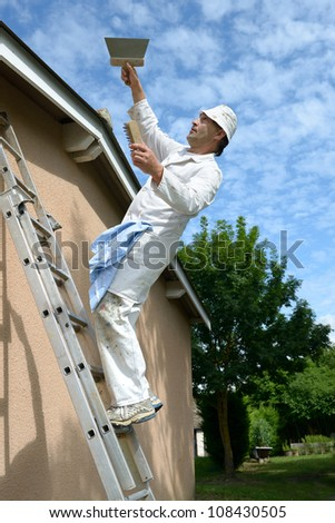 a working house painter who tumbles the ladder - stock photo