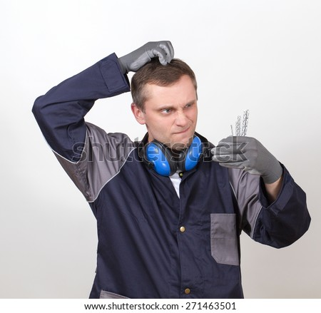 A working man in overalls makes a choice of several pieces. He puzzled scratching his head with a funny expression on his face. - stock photo