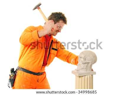 a workman beats a stone skull with a hammer - stock photo