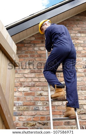 A workman climbing down a ladder at the side of the house - stock photo