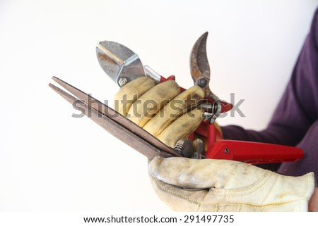 A workman holds used, rusty tools in his gloved hands. - stock photo