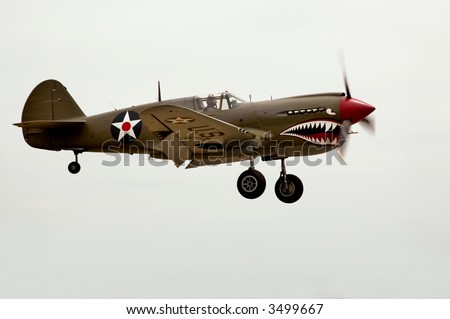 A World War Two P-40 airplane landing at an air show. - stock photo