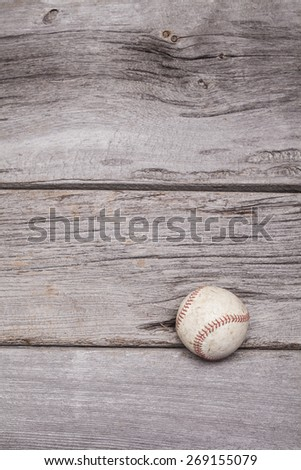 A worn baseball sits on a rustic wooden background. The photograph was shot in portrait format but could be rotated into landscape. - stock photo