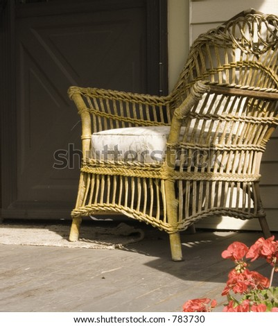 A worn brown wicker rocker is waiting for you on the porch on a bright sunny day. - stock photo