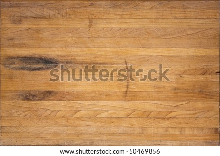 A worn butcher block cutting board sits as a background - stock photo