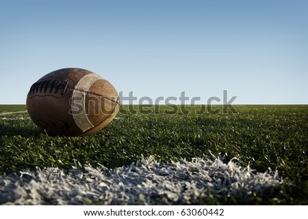 A worn football laying on a grass field with a blue sky. - stock photo