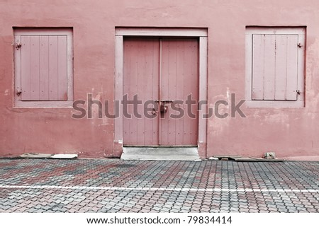 A worn out red color painted entrance with timber doors and windows of the Christ Church building in Melaka city, Malaysia. - stock photo