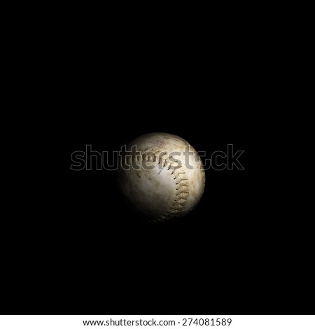 A worn softball sits alone on a solid black background. - stock photo