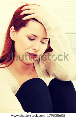 A worried and afraid young woman at home. - stock photo