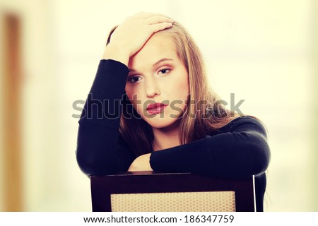 A worried and afraid young woman sitting on chair. - stock photo