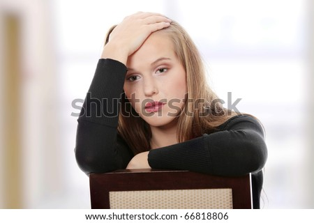 A worried and afraid young woman sitting on chair.