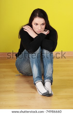 A worried and afraid young woman sitting on the floor. - stock photo