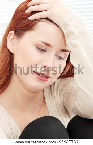 A worried and afraid young woman sitting on the flor. - stock photo