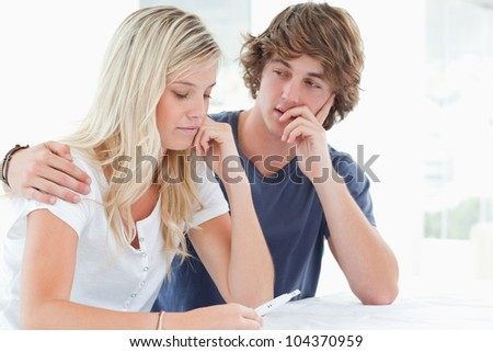 A worried couple embracing as they look at a pregnancy test - stock photo