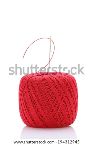 A wound up ball of thread with a needle protruding from the top. - stock photo