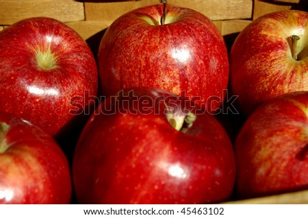 A woven basket filled with ripe, red apples - stock photo